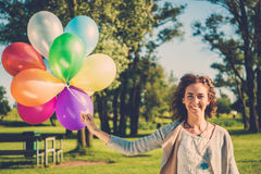 Happy girl with rainbow-colored air balloons in a park. Happy girl with rainbow-colored air balloons in a park Stock Photo