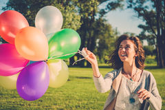 Happy girl with rainbow-colored air balloons in a park. Happy girl with rainbow-colored air balloons in a park Royalty Free Stock Photo