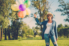 Happy girl with rainbow-colored air balloons in a park. Happy girl with rainbow-colored air balloons in a park Royalty Free Stock Image