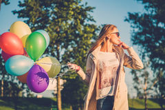 Happy girl with rainbow-colored air balloons in a park. Happy girl with rainbow-colored air balloons in a park Royalty Free Stock Photography
