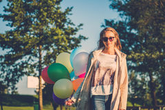 Happy girl with rainbow-colored air balloons in a park. Happy girl with rainbow-colored air balloons in a park Stock Photography