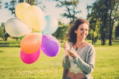 Girl with rainbow-colored air balloons in a park. Royalty Free Stock Image