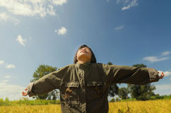Happy girl with raised arms in green spring field against blue sky. Freedom and happiness concept Royalty Free Stock Photos