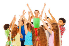Happy girl with raised hands in group of kids Royalty Free Stock Image