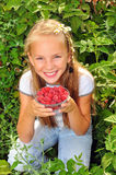Smiling girl holding a bowl of raspberries. Happy girl with raspberries in her hands Stock Photo