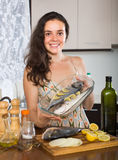 Happy girl with raw fish Stock Photography