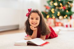 Happy girl reading book at home on christmas Stock Photography