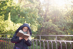 Happy girl reading a book at the railing. Royalty Free Stock Images