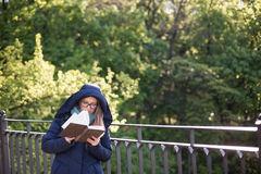 Happy girl reading a book at the railing. Stock Image
