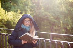 Happy girl reading a book at the railing. Stock Images