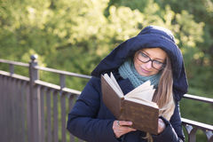 Happy girl reading a book at the railing. Royalty Free Stock Image