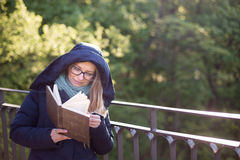 Happy girl reading a book at the railing. Royalty Free Stock Photo