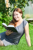 Happy girl reading a book, sitting on green grass Stock Photos