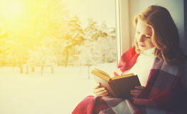 Happy girl reading book by the window in winter Royalty Free Stock Photos