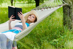 Happy girl reading in hammock in green park outdoors stock image