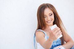 Happy girl reading SMS on your smartphone Royalty Free Stock Photos