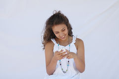A happy girl reading a text. A happy girl having fun looking at her cell phone royalty free stock photography