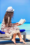 Happy girl reading during tropical white beach Stock Images