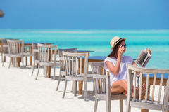 Happy girl reading on tropical white beach Royalty Free Stock Images