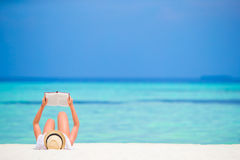 Happy girl reading during tropical white beach Royalty Free Stock Photos