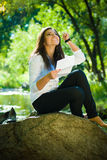 Happy girl reads a letter near garden lake Royalty Free Stock Image