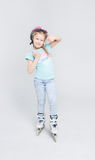 Happy girl ready to roller skate and showing thumbs up at studio. Royalty Free Stock Image