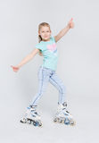 Happy girl ready to roller skate and showing thumbs up at studio. Royalty Free Stock Photography