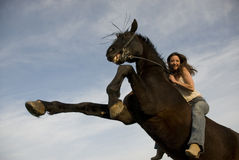 Happy girl and rearing stallion Stock Images