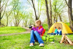 Happy girl with red backpack holds binocular. Near the wooden bonfire and yellow tent during camping in summer weather Royalty Free Stock Photos