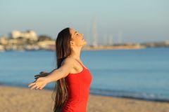 Happy girl in red breathing fresh air on the beach stock image