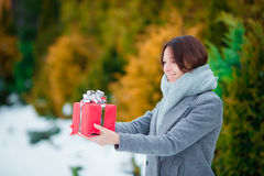 Happy girl with red christmas box gift in winter day outdoors Stock Image