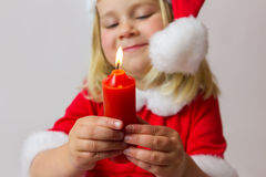 Happy girl with red Christmas candle Royalty Free Stock Photos