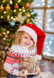 Happy girl in red christmas hat with gift box Royalty Free Stock Photos