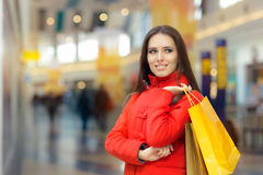 Happy Girl in a Red Coat Shopping in a Mall Royalty Free Stock Photos