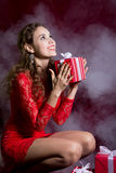 Happy girl in red dress with gift box looking up Stock Photography