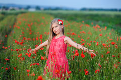 Happy girl in a red dress on poppy field Royalty Free Stock Photo