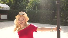 Happy girl in red dress spinning around a lamppost stock video footage