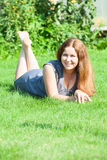 Happy girl with red hair lying on grass and smiling Royalty Free Stock Photography