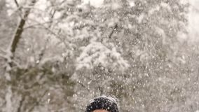Happy girl is spinning under the heavy snow. A happy girl in a red jacket and a black hat toss snow into the sky and spinning under the falling snow stock video
