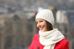 Happy girl in red looking away outdoors in winter. In a town royalty free stock photo