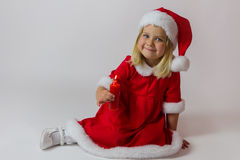 Happy girl in a red new year costume. Happy girl in red new year cap posing in studio with Christmas candle Royalty Free Stock Photos