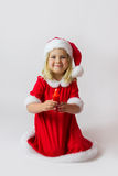 Happy girl in a red new year costume. Happy girl in red new year cap posing in studio with Christmas candle Stock Images