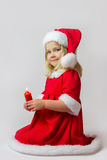 Happy girl in a red new year costume. Happy girl in red new year cap posing in studio with Christmas candle Stock Image