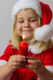 Happy girl in a red new year costume. Happy girl in red new year cap posing in studio with Christmas candle Stock Photo