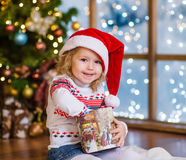 Happy girl in red santa hat opening Christmas gifts Royalty Free Stock Photography
