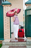 Happy girl with a red suitcase. Leaves gate of the house Stock Photography