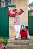 Happy girl with a red suitcase. Leaves gate of the house Royalty Free Stock Photo