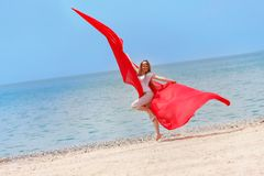 Happy girl with red wings jumping on beach Stock Photography