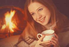 Happy girl relax by fireplace with mug of warming tea, coffee in winter Stock Image