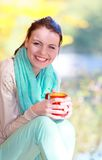 Happy girl relaxing in the autumn park enjoying hot drink Stock Images